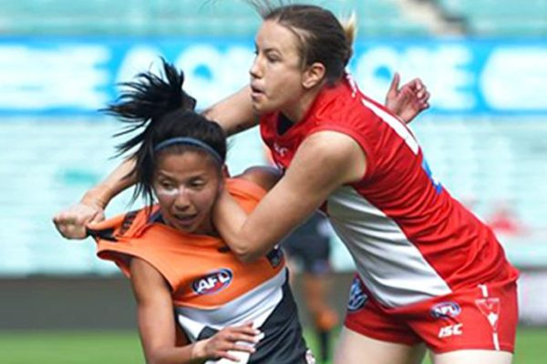 Photo taken on April 9, 2016 shows Australian rules women football players, Mai Nguyen of the Greater Western Sydney Giants (L) and Kim Hemenway of the Sydney Swans (R) playing an exhibition match at the Sydney Cricket Ground in Sydney. It has taken almost 160 years since the first Australian Rules football club was formed, but women are finally set to join one of the last bastions of male-dominated sport Down Under when a female national league is launched next year. / AFP / PETER PARKS / TO GO WITH AFP SOTRY: Australia-women-AFL-AUS, FEATURE by Glenda Kwek        (Photo credit should read PETER PARKS/AFP/Getty Images)